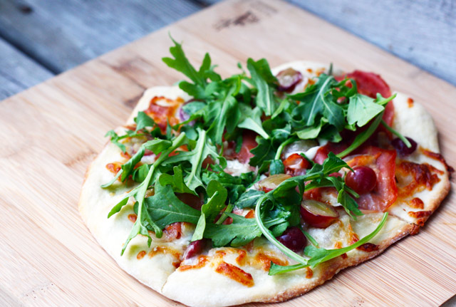 Grape, prosciutto, and arugula flatbread recipe, an appetizer or main course. Repin to save!