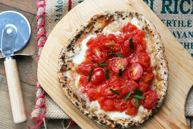 Bruschetta-style pita pizzas. Fresh garlic and tomatoes make this pizza taste like bruschetta. YUM!