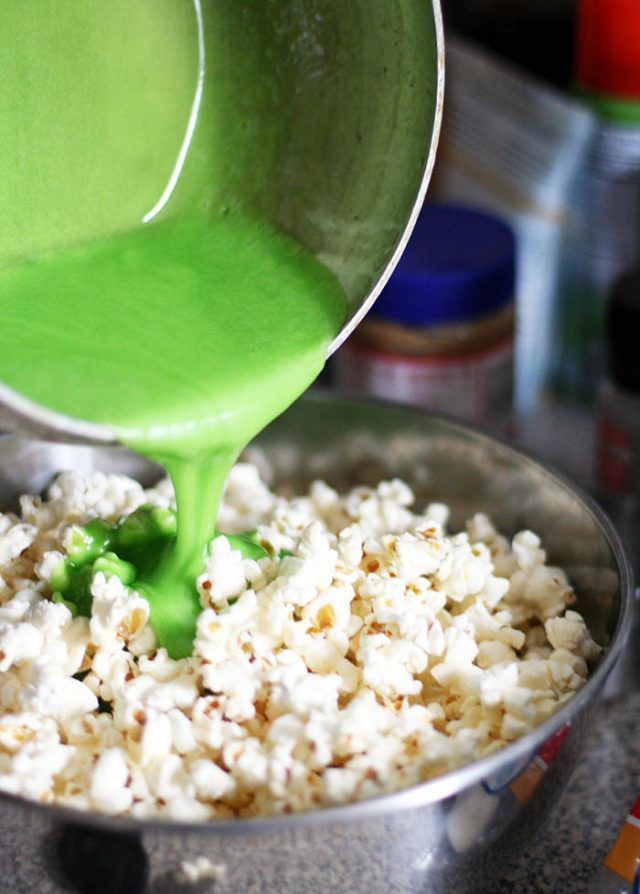 Green marshmallow mixture is added to popcorn to make a Christmas tree popcorn!