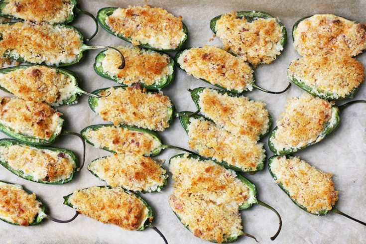 Baked jalapeño poppers with whipped cream cheese, bacon, cheddar, and topped with panko breadcrumbs! Click through for recipe.